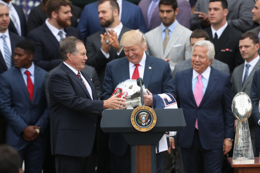 . New England Patriots head coach Bill Belichck presents President Donald Trump with a Patriots helmet during a ceremony on the South Lawn of the White House in Washington, Wednesday, April 19, 2017, where the president honored the Super Bowl Champion New England Patriots for their Super Bowl LI victory. Patriots owner Robert Kraft is at right. (AP Photo/Andrew Harnik)