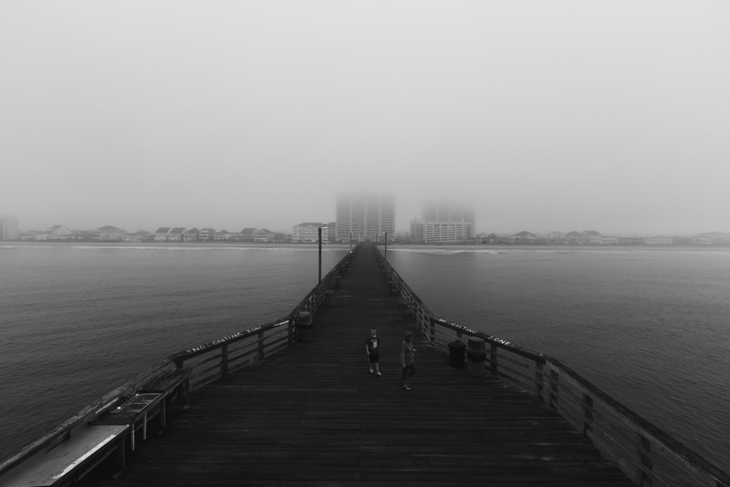 a child walks with his mother on the pier before day.