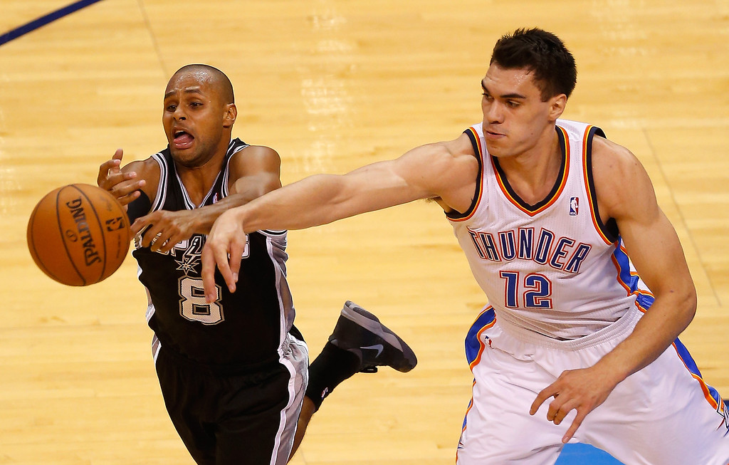 . OKLAHOMA CITY, OK - MAY 31:  Patty Mills #8 of the San Antonio Spurs battles for the ball with Steven Adams #12 of the Oklahoma City Thunder in the second half during Game Six of the Western Conference Finals of the 2014 NBA Playoffs at Chesapeake Energy Arena on May 31, 2014 in Oklahoma City, Oklahoma. (Photo by Tom Pennington/Getty Images)