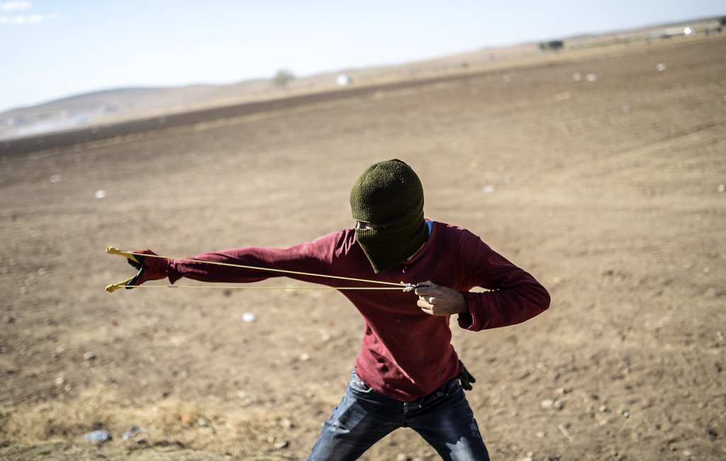 . A Kurdish protestor uses a sling shot against Turkish soldiers near the Syrian border after Turkish authorities temporarily closed the border at the southeastern town of Suruc in Sanliurfa province, on September 22, 2014. BULENT KILIC/AFP/Getty Images