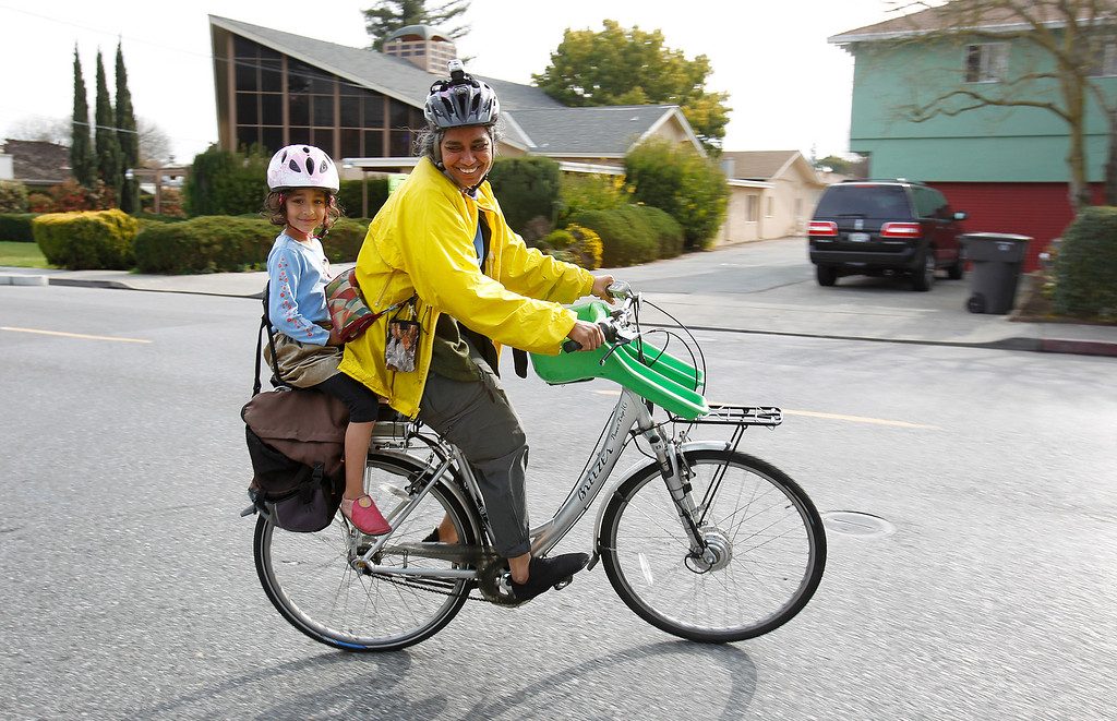 . From right, Kalyanaraman Shankari and Jayalakshmi Raffill, 5, enjoy their ride during the Great Streets Rengstorff Park Neighbor Bike Tour in Mountain View, Calif. on Sat., March 2, 2013. (LiPo Ching/Staff)
