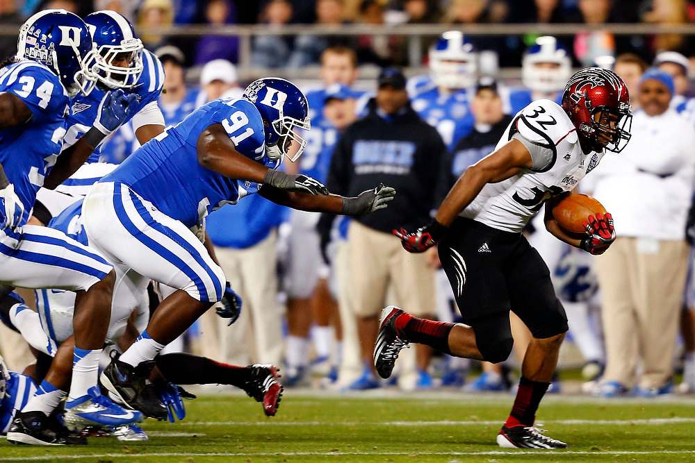 . Cincinnati\'s Pat O\'Donnell (34) runs past Duke\'s Jamal Bruce (91) and Jonathan Woodruff (34) during the first half of the Belk Bowl NCAA college football game in Charlotte, N.C., Thursday, Dec. 27, 2012. (AP Photo/Chuck Burton)