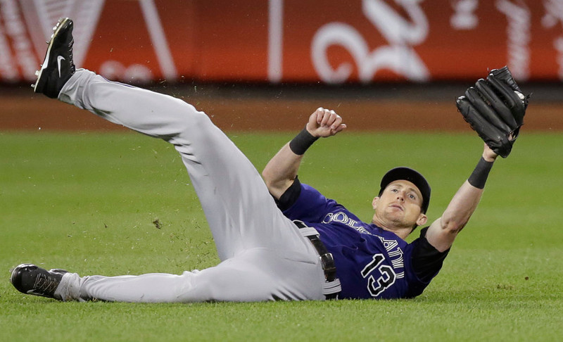 . Colorado Rockies center fielder Drew Stubbs (13) shows the ball after making a sliding catch of Mets pinch hitter Matt den Dekker\'s seventh-inning fly out in a baseball game in New York, Monday, Sept. 8, 2014. (AP Photo/Kathy Willens)