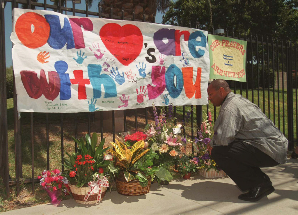 . Naji Ali of Los Angeles takes a look at flowers and signs placed in sympathy outside the Jewish Community Center in Granada Hills.   Los Angeles Daily News file photo.