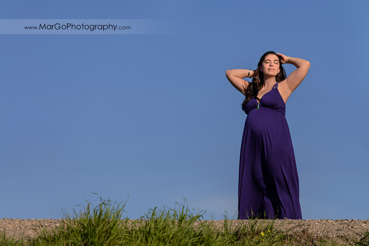 pregnant woman in long violet dress on top of the green hill during maternity session at Ulistac Natural Area in Santa Clara