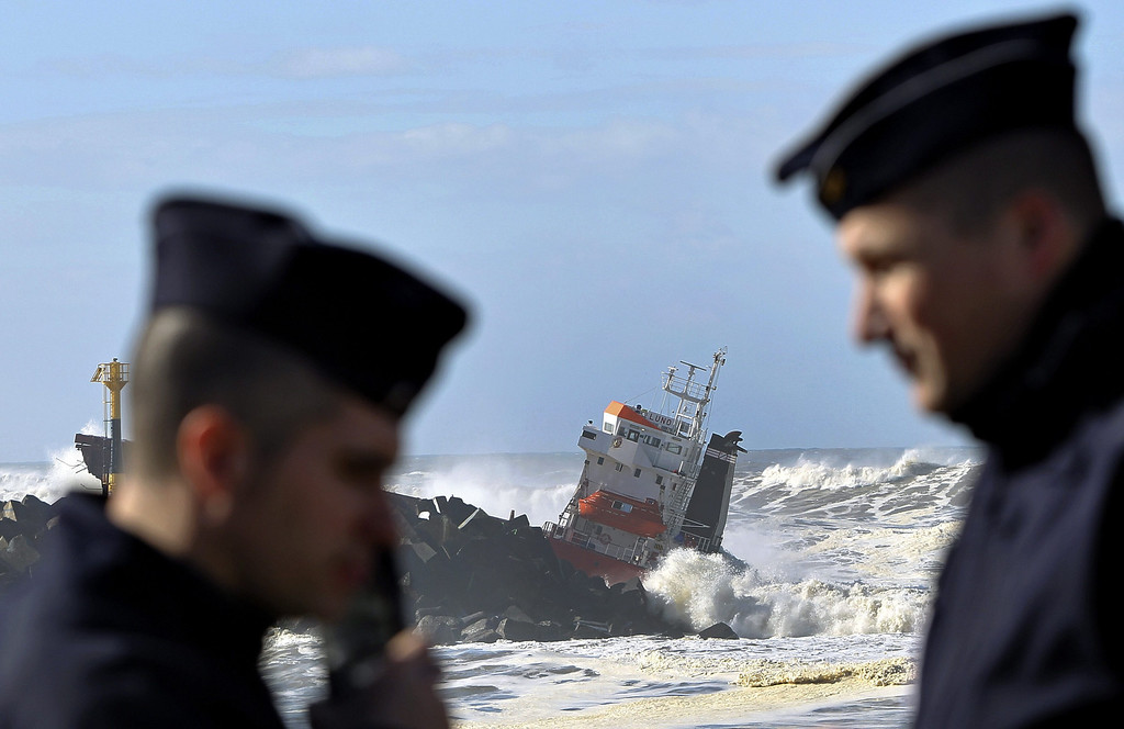 . Waves batter the stricken Spanish freighter Luno (in the background) as two French policemen watch over the scene in front of  Bayonne harbor, south west France 5 February 2015.  It is believed the vessel struck the breakwater after drifting following engine failure. All 21 crew members were winched to safety by helicopter  EPA/Javier Etxezarreta