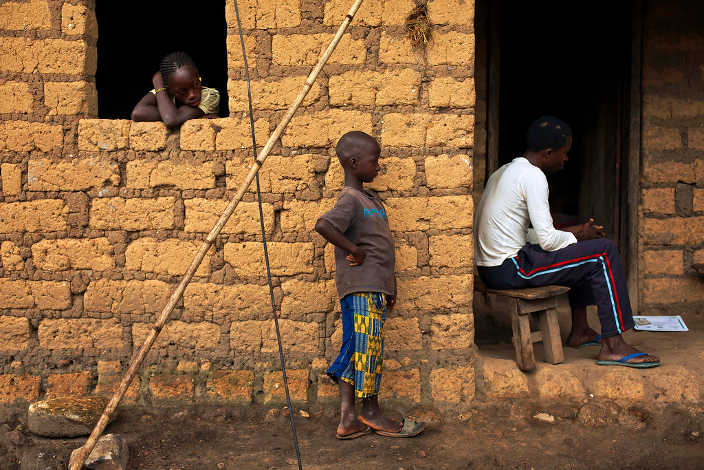 . In this photo taken Sunday Nov. 23, 2014, Lansana Kamano, right, a traditional healer, sits in the Guinean village of Meliandou, some 400 miles (600 kms) south-east of Conakry, Guinea, believed to be Ebola\'s ground zero. (AP Photo/Jerome Delay)