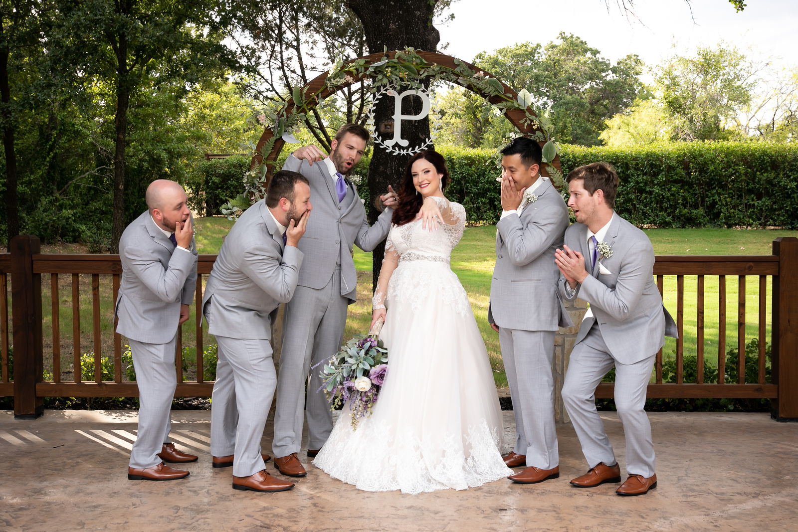five groomsmen wearing grey suits with cognac colored shoes jokingly aweing at the bride's wedding ring