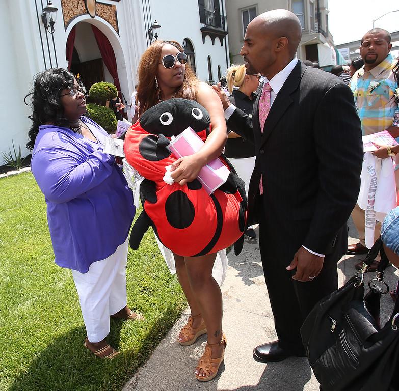 . Chiquita Carradine, center, holds onto a stuffed ladybug as she leaves McNary-Williams-Jackson Mortuary  after funeral services for her daughter Alaysha Carradine ,8, on Tuesday, July 30, 2013 in Oakland, Calif.  Alaysha Carradine was shot and killed during a sleepover at a friends house in the 3400 block of Wilson Avenue earlier this month in Oakland.   (Aric Crabb/Bay Area News Group)