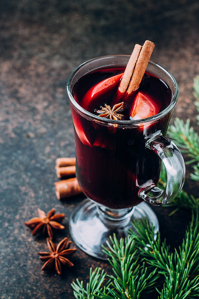 Two Glasses Of Hot Mulled Wine With Spices And Sliced Orange And Apple On Stone Concrete Table Backg
