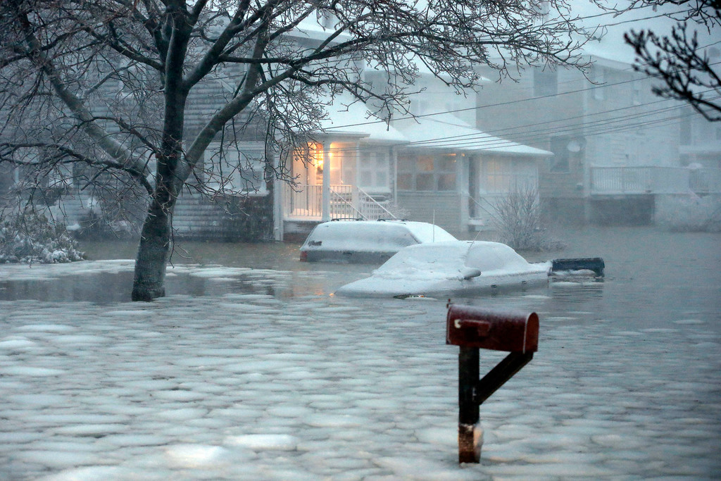 . Water floods a street on the coast in Scituate, Mass., Tuesday, Jan. 27, 2015. A storm packing blizzard conditions spun up the East Coast early Tuesday, pounding parts of coastal New Jersey northward through Maine with high winds and heavy snow. (AP Photo/Michael Dwyer)