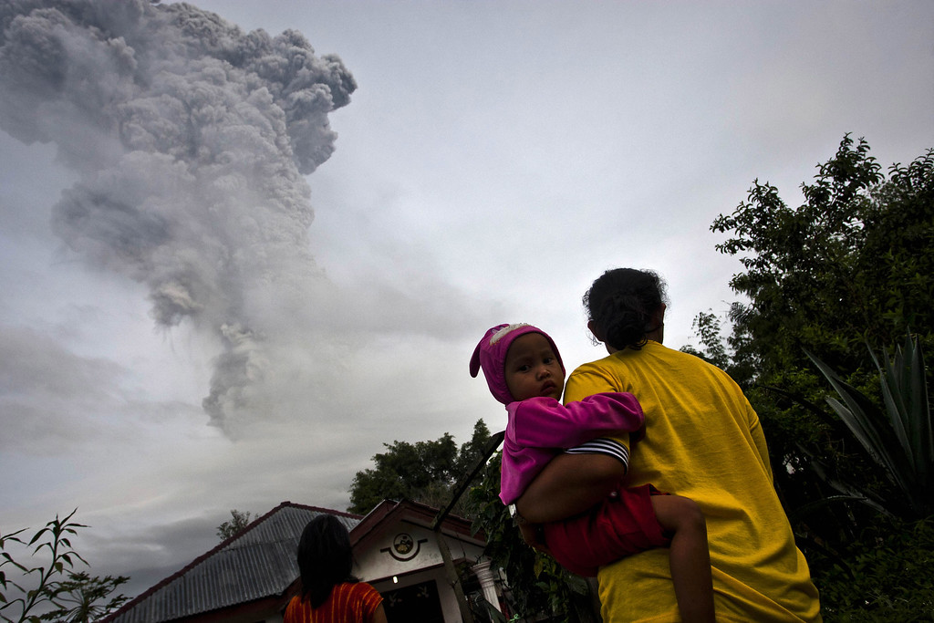 . A woman carries her daughter as Mount Sinabung spews pyroclastic smoke seen from Tigapancur village in Karo district on November 14, 2013 in Medan, Sumatra, Indonesia. Up to 4,300 residents have been evacuated from five villages in North Sumatra due to the volcanic eruptions of Mount Sinabung. The volcano has been erupting for several days, spewing ash and lava 2.5 miles into the sky.  (Photo by Ulet Ifansasti/Getty Images)