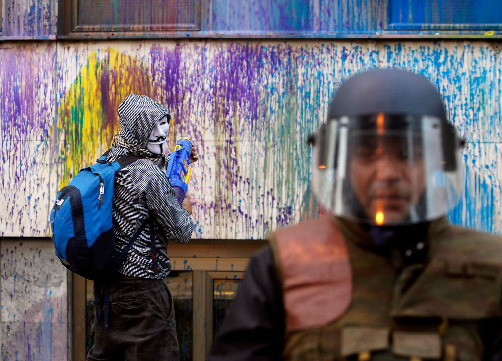 . A protestor uses a water gun to spray with colored paint the facade of the Public Revenue Office building behind the police cordon, during an anti-government protest in downtown Skopje, Macedonia, Tuesday, May 10, 2016. Protests continue in the Balkan country almost every evening for nearly a month, after the country\'s president pardoned dozens of politicians who were facing criminal proceedings for alleged involvement in a wiretapping scandal. (AP Photo/Boris Grdanoski)