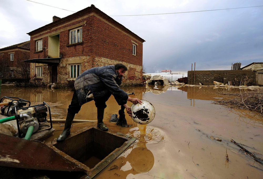 Description of . A man drains water out of his flooded house in Murtino, 180 km east of capital Skopje February 27, 2013. One man drowned and several hundred homes in Macedonia were flooded on Tuesday as two days of heavy rain drenched farmland and caused power outages in the Balkan country, authorities said.  REUTERS/Ognen Teofilovski