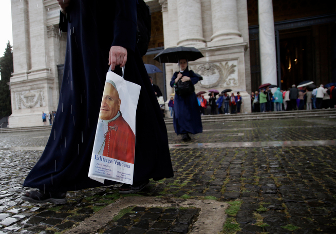 . A nun holds a plastic bag adorned with a picture of late Pope John XXIII next to St. John in Lateran Basilica  in Rome, Saturday, April 26, 2014. Hundred thousands of pilgrims and faithful are expected to reach Rome to attend the scheduled April 27 ceremony at the Vatican in which Pope Francis will elevate in a solemn ceremony John XXIII and John Paul II to sainthood. (AP Photo/Gregorio Borgia)