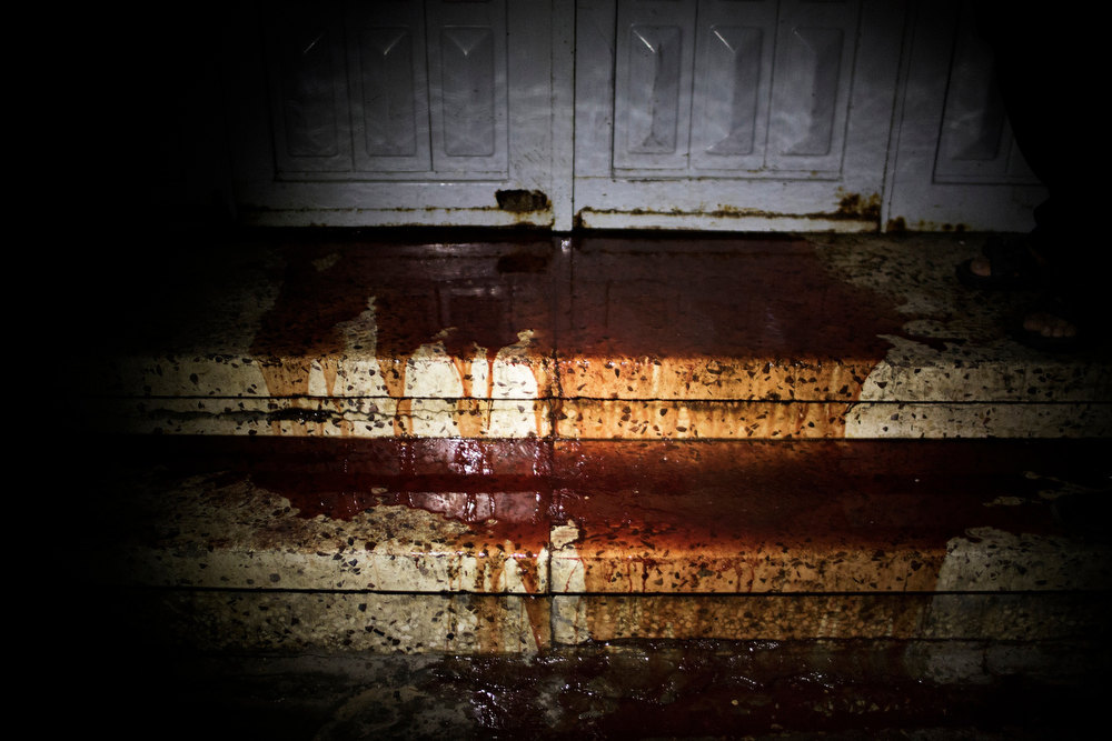 . Blood leaks from under the door of the al-Shifa hospital morgue in Gaza City on November 20, 2012. Two cameramen from Hamas-owned Al-Aqsa TV were among six people killed in Israeli air raids on the Gaza Strip, raising Tuesday\'s death toll to 20, a Hamas spokesman said. MARCO LONGARI/AFP/Getty Images