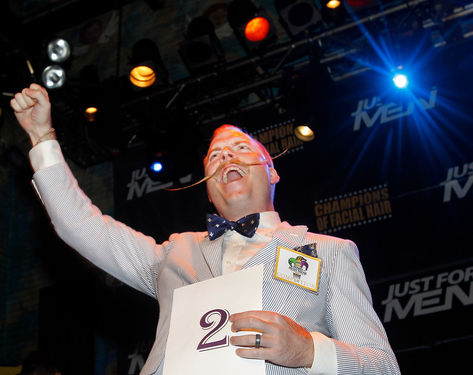 . Nick Ackerman celebrates taking the gold for first place in the English Moustache division during the fourth annual Just For Men National Beard and Moustache Championships Saturday, Sept. 7, 2013 at The House of Blues in New Orleans. Contestants competed in 18 different categories including Dali, full beard natural and sideburns. (AP Photo/Susan Poag)