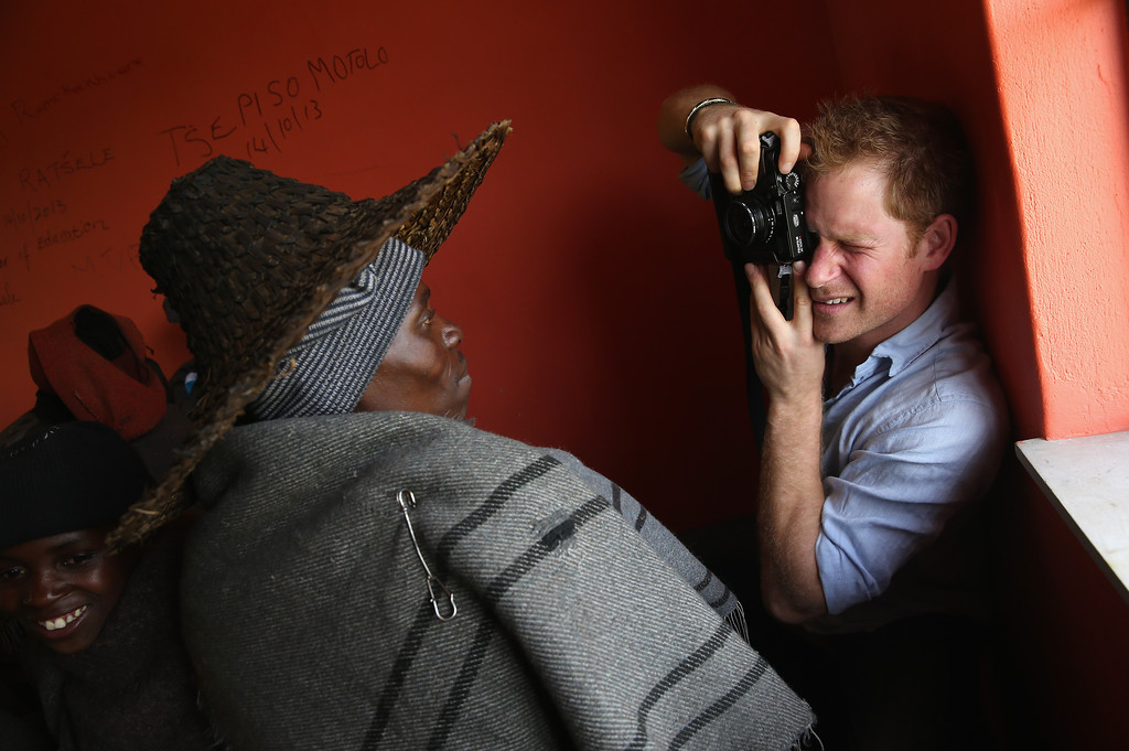 ". Prince Harry takes a photograph on a Fuji X100s Camera during a visit to a herd boy night school constructed by Sentebale on December 8, 2014 in Mokhotlong, Lesotho. Speaking of the opportunity to document the visit himself, Prince Harry said: ""I have always enjoyed photography and the challenges that come with trying to capture the perfect shot, although privately I don\'t take many photos. The best photos I have are in my head - I have some very special memories, mostly from Africa. But on this visit, I had the time and opportunity to be on the other side of the camera and take some photos in the stunning country of Lesotho for my charity Sentebale.\"" (Photo by Chris Jackson - WPA Pool /Getty Images)"