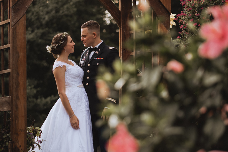 The bride and groom smile lovingly into one another's eyes under an arbor.