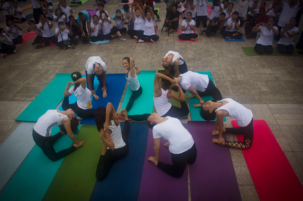. A group of people demonstrate yoga on International Yoga Day, in Yangon, Myanmar Wednesday, June 21, 2017. Yoga enthusiasts took part in mass yoga programs to mark International Yoga Day throughout the world. (AP Photo/Thein Zaw)