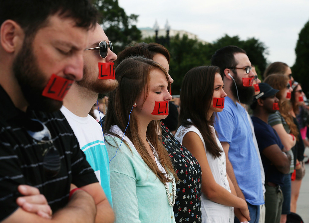 . Pro-life protesters stand with red tape over their mouths in front of the U.S. Supreme Court, June 30, 2014 in Washington, DC.  (Photo by Mark Wilson/Getty Images)
