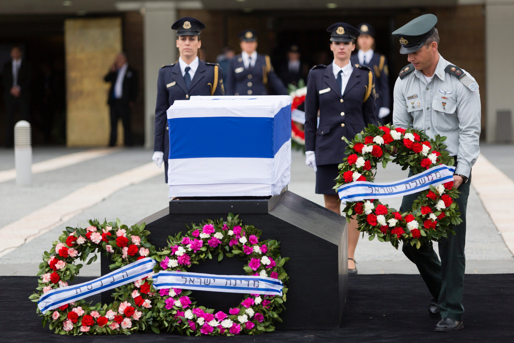 . An Israeli military officer arranges the wreaths laid on the coffin of former Israeli Prime Minister Ariel Sharon as it lies in state at the Knesset, Israel\'s Parliament, on January 12, 2014 in Jerusalem, Israel.(Photo by David Vaaknin/Getty Images)