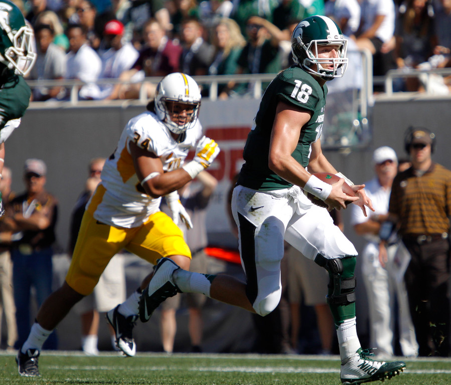 . Michigan State quarterback Connor Cook (18) scrambles against Wyoming\'s Siaosi Hala\'api\'api during the first quarter of an NCAA college football game, Saturday, Sept. 27, 2014, in East Lansing, Mich. Michigan State won 56-14. (AP Photo/Al Goldis)