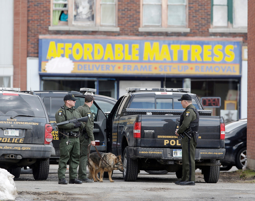 . Law enforcement officers stand in an alley near Main Street while searching for a suspect in two shootings that killed four and injured at least two on Wednesday, March 13, 2013.  (AP Photo/Mike Groll)