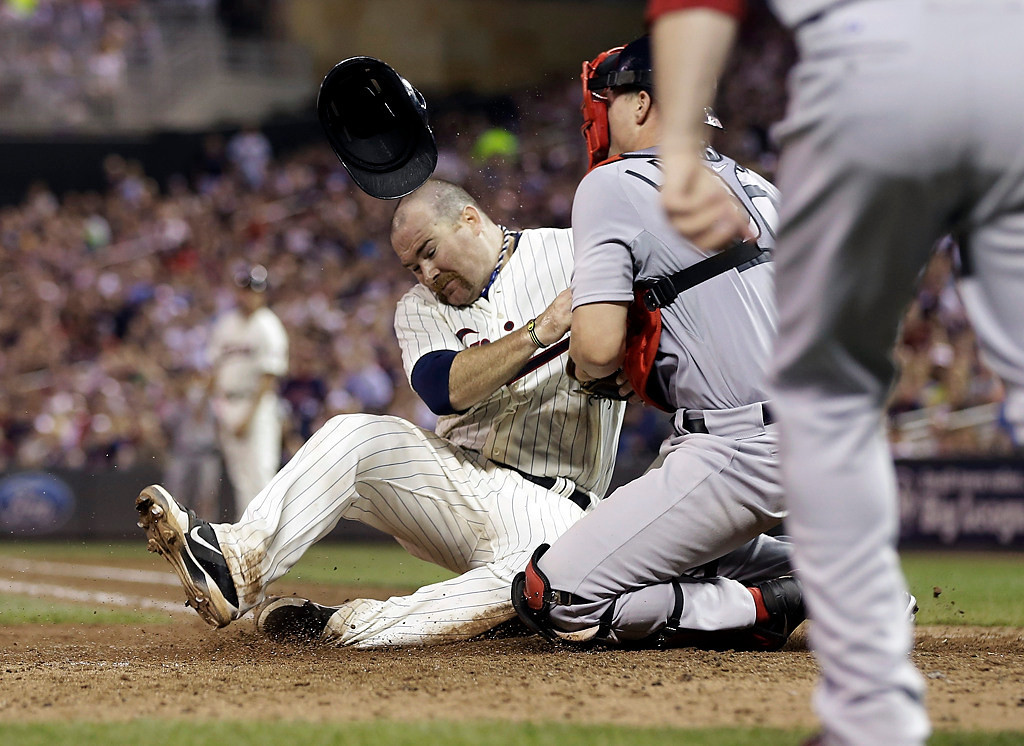 . Minnesota Twins\' Ryan Doumit, loses his helmet as he collides with Boston Red Sox catcher Ryan Lavarnway, who tagged Doumit out as he tried to score from third on a fly out by Aaron Hicks in the sixth inning. (AP Photo/Jim Mone)