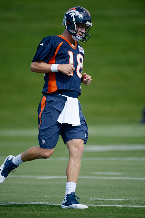 . Denver Broncos quarterback Peyton Manning (18) runs through drills during the first day of the Denver Broncos 2014 training camp July 24, 2014 at Dove Valley. (Photo by John Leyba/The Denver Post)