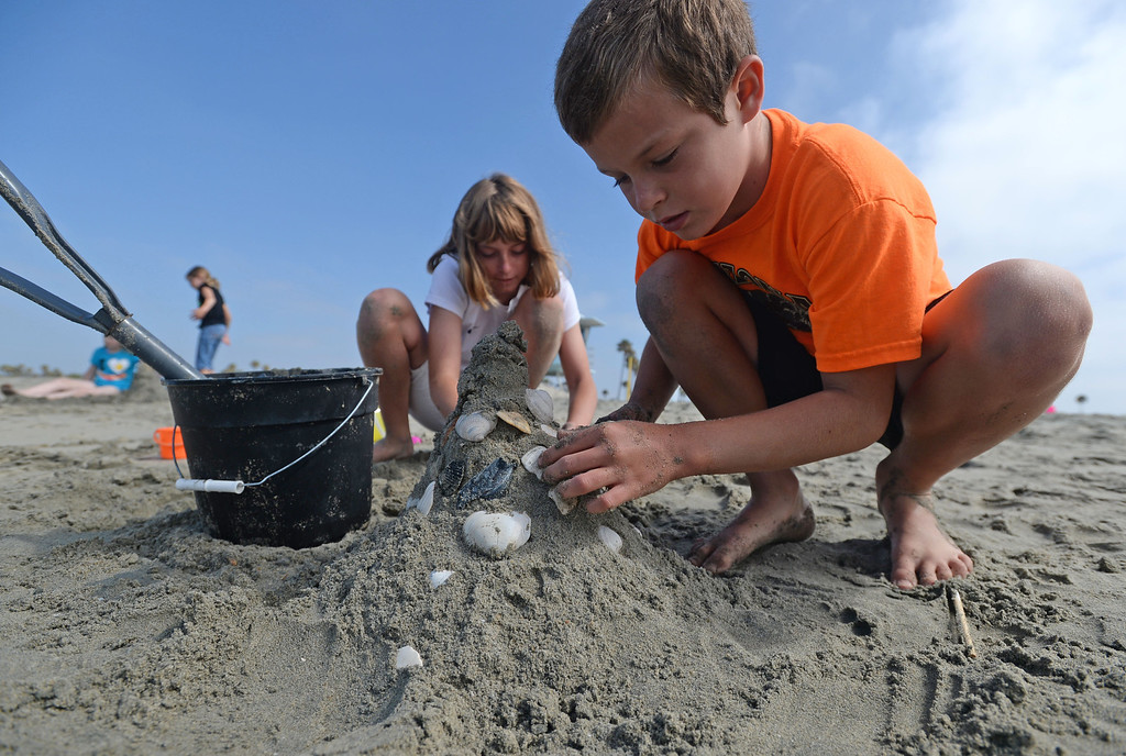 . Children had a chance to hone their sand castle building skills in a sand castle camp Monday at Granada Beach in Belmont Shore. Daniel Gates, 9, and his sister Nicole Gates, 12, of Long Beach, add seashells found on the beach to their castles. 20130805 Photo by Steve McCrank / Staff Photographer