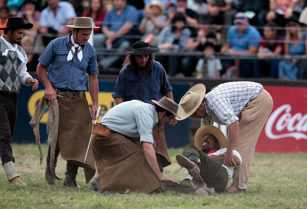 ". A gaucho reacts in pain after being unseated by an unbroken horse as others help him during the annual celebration of Criolla Week in Montevideo, March 25, 2013. Throughout Easter Week ""gauchos\"", the Latin American equivalent of the North American \""cowboy\"", from all Uruguay and neighboring Argentina and Brazil visit Montevideo to participate in Criolla Week to win the award of best rider. The competition is held March 24 - March 30. REUTERS/Andres Stapff"