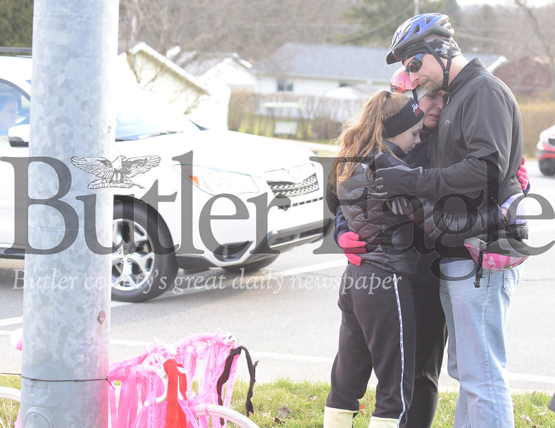 """Christina Teimouri, left, is consoled as she is overcome with emotion while visiting the site of a """"ghost bike"""" memorial for her son, Alek."""