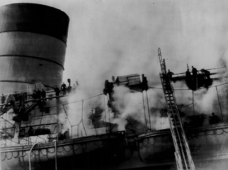 . Firemen fight through smoke to battle a blaze aboard liner Queen Elizabeth in Southampton, England on Mer. 19,1946. Officials of the Cunard White Star Line, owner of the craft, hinted the fire was the result of sabotage. (AP Wirephoto)