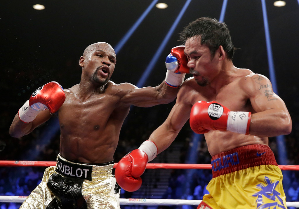 . Floyd Mayweather Jr., left, hits Manny Pacquiao, from the Philippines, during their welterweight title fight on Saturday, May 2, 2015 in Las Vegas. (AP Photo/Isaac Brekken)