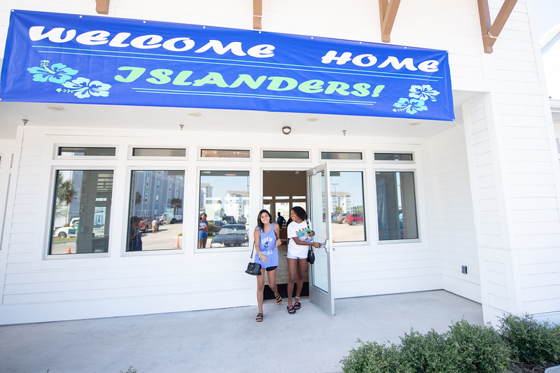 Valeria Ruiz (left), and Uosmari Lima stop by the Momentum Village club house to pick up the keys to their new rooms.