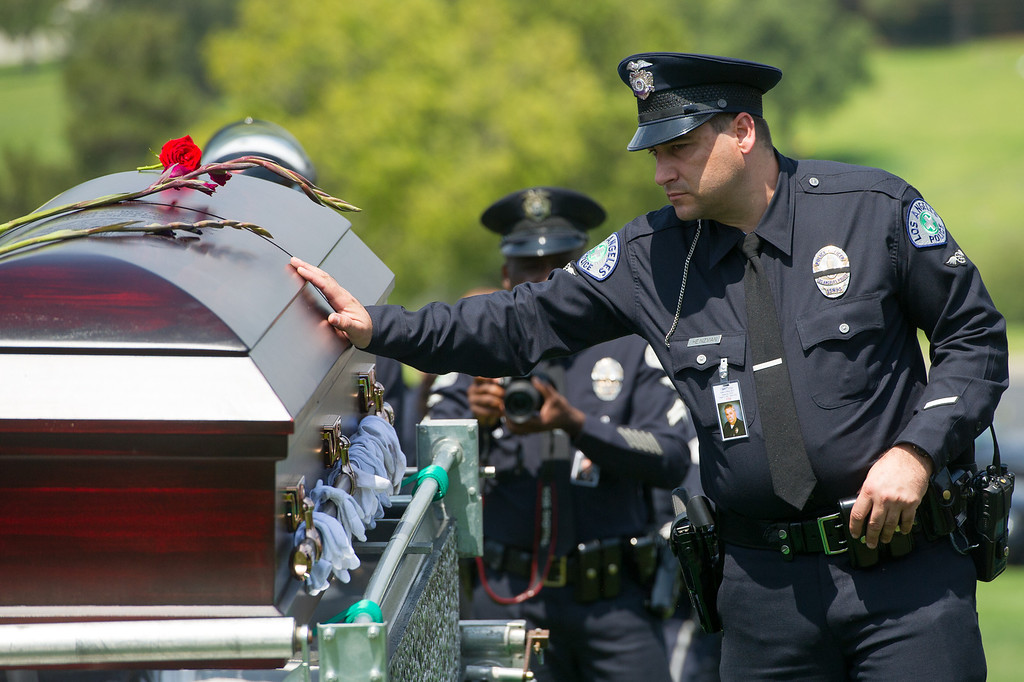 . LAPD officers touch the casket of LAPD officer Chris Cortijo, Tuesday, April 22, 2014, at Forest Lawn Hollywood Hills. (Photo by Michael Owen Baker/L.A. Daily News)