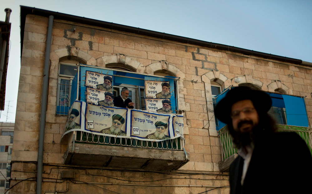 Description of . An Ultra Orthodox Jewish man walks past another standing in a balcony decorated with pictures of Rabbi Ovadia Yosef, the Jewish spiritual leader of Israel's Shas party, on election day for Israel's parliament in Jerusalem, Tuesday, Jan. 22, 2013. Israelis began trickling into polling stations Tuesday morning to cast their votes in a parliamentary election expected to return Prime Minister Benjamin Netanyahu to office despite years of stalled peacemaking with the Palestinians and mounting economic troubles. (AP Photo/Sebastian Scheiner)