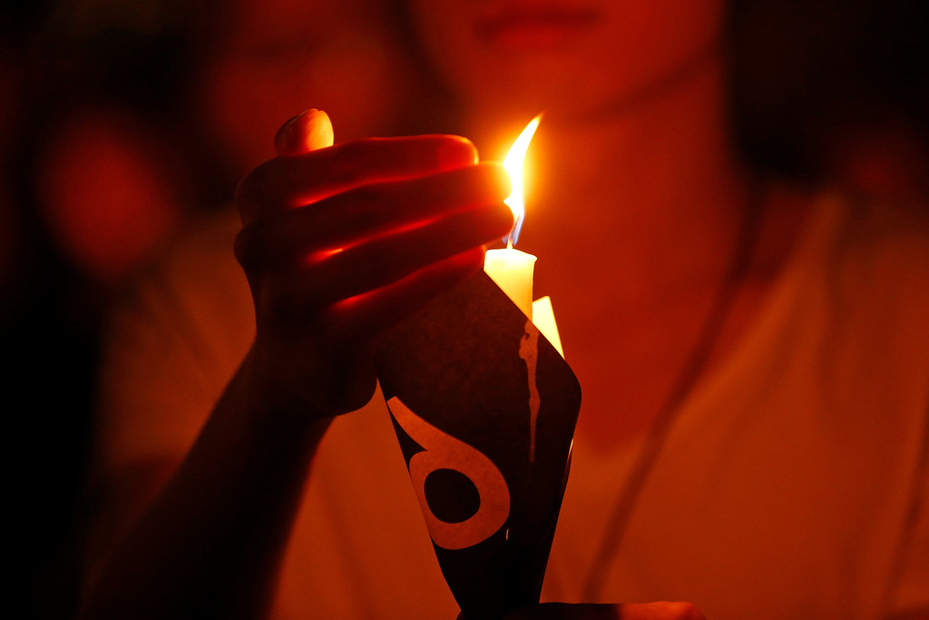 . A woman holds a candle as tens of thousands of people attend a candlelight vigil at Victoria Park in Hong Kong Wednesday, June 4, 2014 to mark the 25th anniversary of the June 4th Chinese military crackdown on the pro-democracy movement in Beijing. (AP Photo/Kin Cheung)