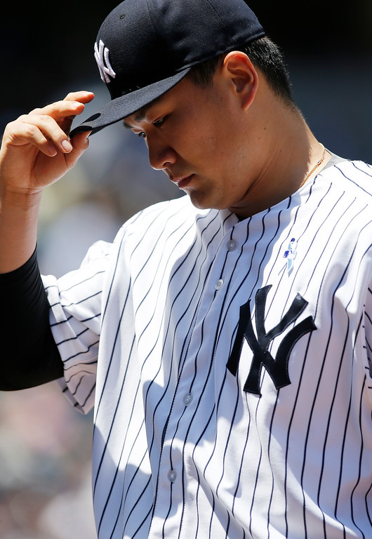 . New York Yankees starting pitcher Masahiro Tanaka retreats to the dugout during the Yankees 12-4 loss to the Detroit Tigers in a baseball game at Yankee Stadium in New York, Sunday, June 21, 2015.  (AP Photo/Kathy Willens)