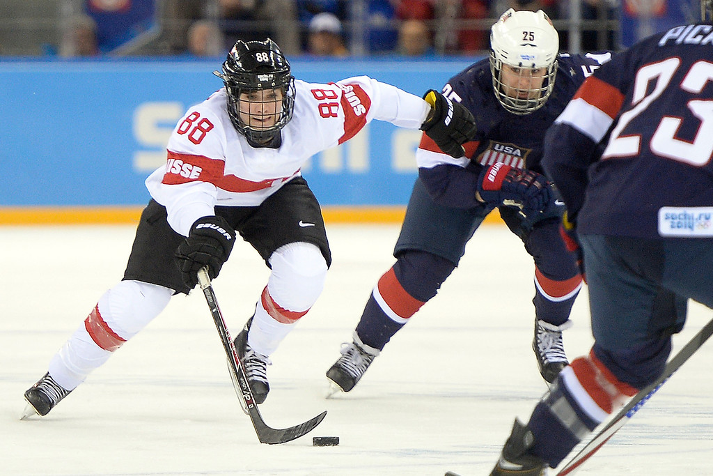 . Phoebe Stanz (88) of the Switzerland skates away from the defense of Alex Carpenter (25) of the U.S.A. during the first period of action at the Shayba Arena. Sochi 2014 Winter Olympics on Monday, February 10, 2014. (Photo by AAron Ontiveroz/The Denver Post)