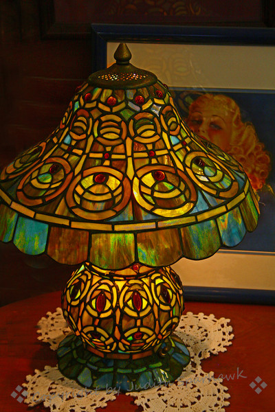 "The Lamp and the Blonde ~ This was one of several stained glass lamps in an antique shop along Route 66.  I liked the way it not only lit up, but also cast a pattern on the picture of ""the blonde"" behind it."