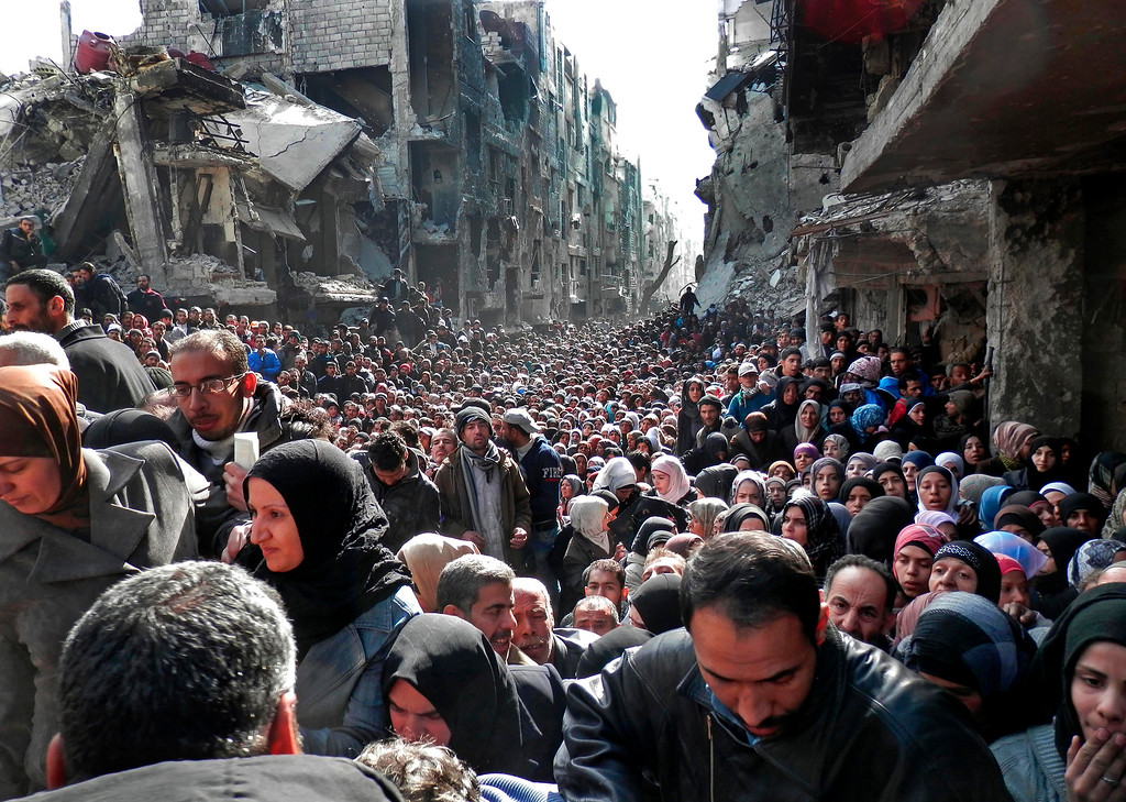 . This picture taken on Jan. 31, 2014, and released by the UNRWA, shows residents of the besieged Palestinian camp of Yarmouk, queuing to receive food supplies, in Damascus, Syria. A United Nations official called on warring sides in Syria to allow aid workers to resume distribution of food and medicine in a besieged Palestinian district of Damascus. The call comes as U.N. Secretary General Ban Ki-Moon urged Syrian government to authorize more humanitarian staff to work inside the country, devastated by its 3-year-old conflict. (AP Photo/UNRWA, File)