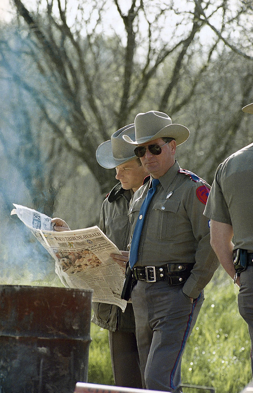 . Two Texas Department of Public Safety officers read the morning paper at a road block near the Branch Davidian compound outside Waco, Texas on Friday, April 2, 1993. The standoff between federal agents and the Branch Davidians has continued for almost five weeks (AP Photo/Susan Weems)