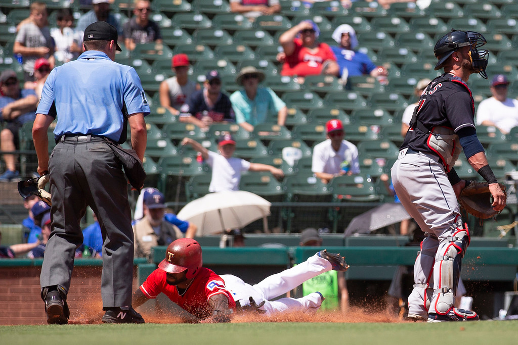 . Texas Rangers\' Delino DeShields, center, scores a run during the fifth inning of a baseball game against the Cleveland Indians, Sunday, July 22, 2018, in Arlington, Texas. (AP Photo/Sam Hodde)