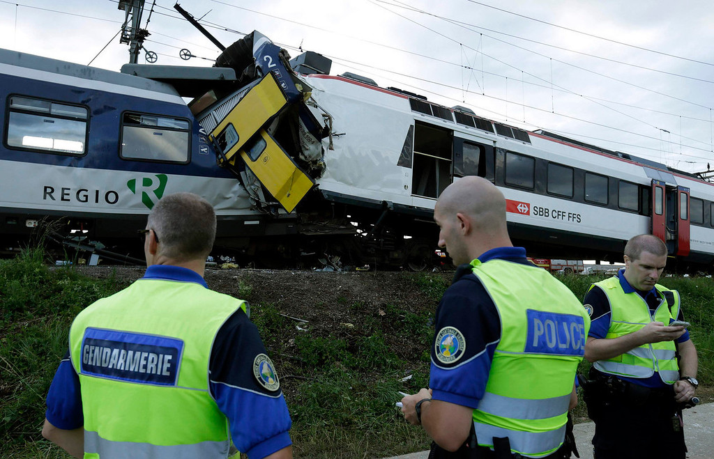 . Police officers and rescue workers are pictured at the site of a head on collision between two trains near Granges-pres-Marnand, near Payerne in western Switzerland, July 29, 2013. The two trains collided at Granges-pr�s-Marnand in the Swiss canton of Vaud on Monday evening, injuring about 40 people, four seriously, Swiss news agency ATS reported. There was no immediate report of any deaths in the crash. REUTERS/Denis Balibouse  (SWITZERLAND - Tags: DISASTER TRANSPORT)