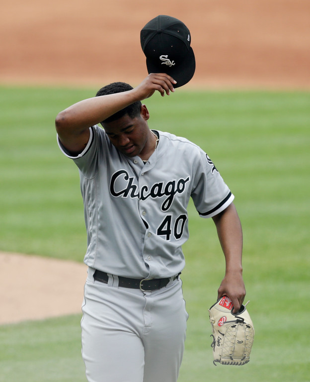 . Chicago White Sox starting pitcher Reynaldo Lopez wipes his forehead as he walks to the dugout in the third inning of a baseball game against the Cleveland Indians, Wednesday, May 30, 2018, in Cleveland. (AP Photo/Tony Dejak)