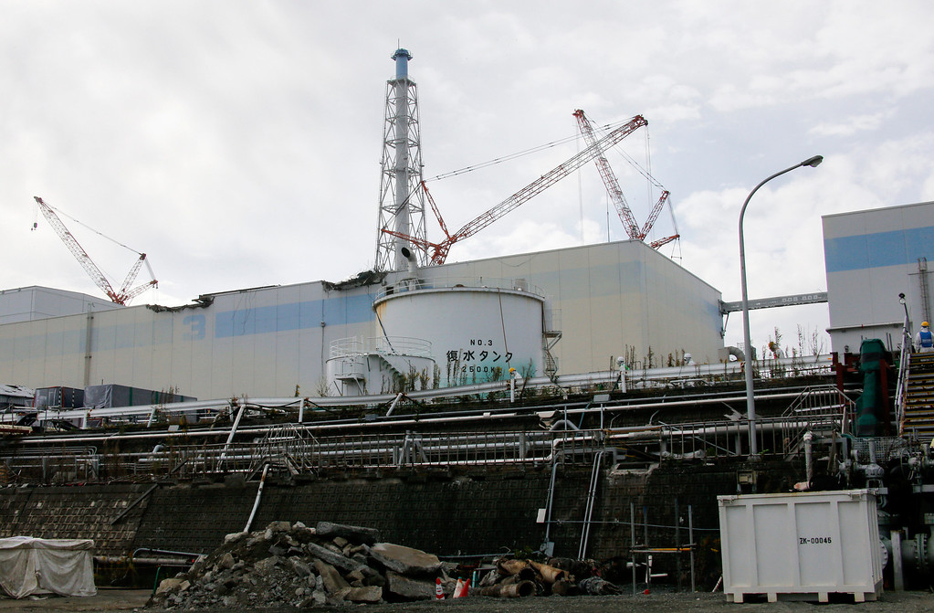 . Workers walk past the nuclear reactor three building seen from the coastal side at Tokyo Electric Power Co.\'s (Tepco) Fukushima Dai-ichi nuclear power plant in Okuma, Fukushima Prefecture, Japan on November 7, 2013.  Nuclear engineers in Japan are preparing to move uranium and plutonium fuel rods at Fukushima, their most difficult and dangerous task since the plant\'s runaway reactors were brought under control two years ago.  AFP PHOTO / KIMIMASA MAYAMA / POOL /AFP/Getty Images