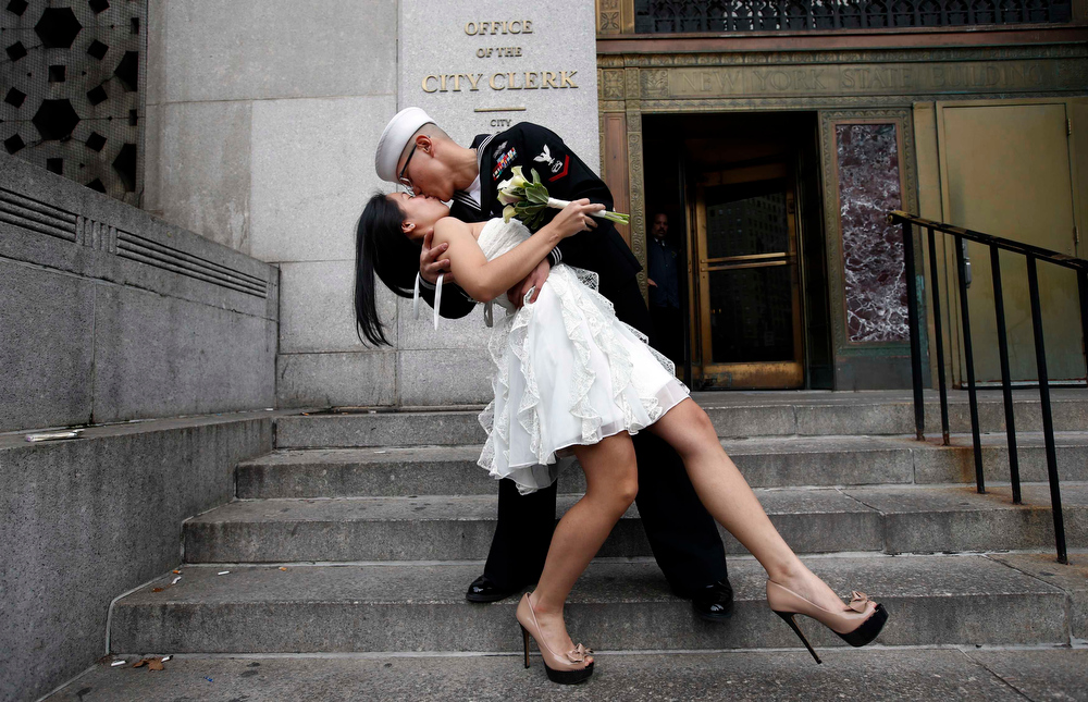 . U.S. Navy Petty Officer 3rd Class EO3 John Chen, 23, from Lakehurst, New Jersey, kisses his new bride Victoria Chan, 25, from Manhattan, after they were married in a civil ceremony at New York City\'s Office of the City Clerk December 12, 2012. Hundreds of couples packed the office in lower Manhattan to be married on the date 12/12/12 as this will be the last such triple date for almost a century until January 1, 2101.  REUTERS/Mike Segar