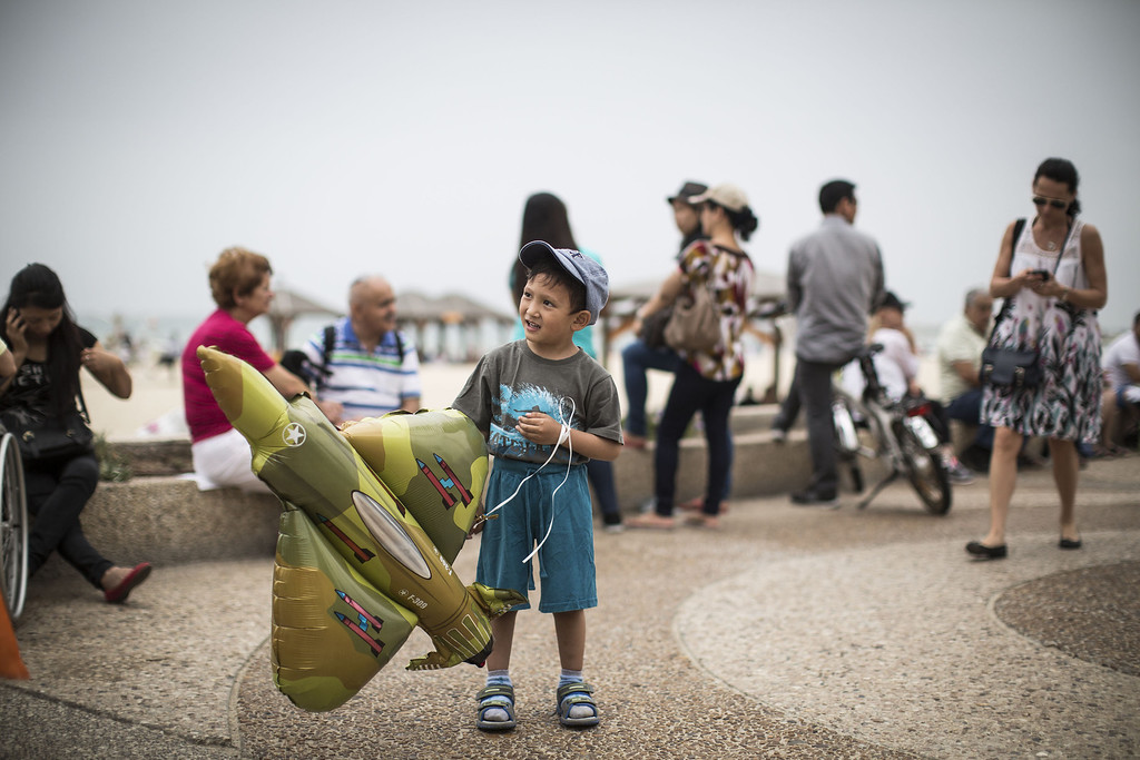 . A young boy plays with a plane-shaped balloon on the beach in the Mediterranean sea as people wait for the  military air show marking the 66th anniversary of Israel\'s independence to start on May 6, 2014 in Tel Aviv, Israel. The day marks when David Ben-Gurion, the Executive Head of the World Zionist Organization declared the establishment of a Jewish state in Eretz- Israel. (Photo by Ilia Yefimovich/Getty Images)